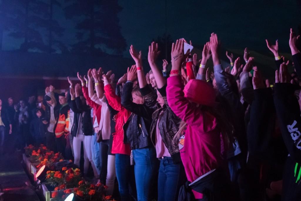 Ulkona on pimeää. Yleisö seuraa esitystä ja nostaa kädet ylös.