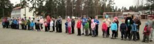 Kuvassa alakoululaiset seisovat rivissä urheilukentällä.