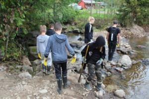 Oppilaita tekemässä lohiportaita Isojokeen lapioiden kanssa. Paikka IIvarinkylä.