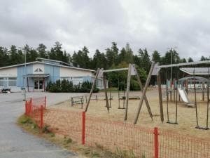Alakoulun leikkikentä keinuja. Etualalla on punainen aita, joka estää lapsia juoksemasta suoraan autotielle. Taka-alalla on koulurakennus.