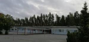 Kuvassa on yläkoulun puoli. Pääsisäänkäynnin edessä on lippa, jonka alla oppilaat viettävät välituntia sateen sattuessa.