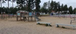 Alakoulun leikkipihan keinuja ja kiipeilytelineitä. Piha on pinnoitettu hiekalla.