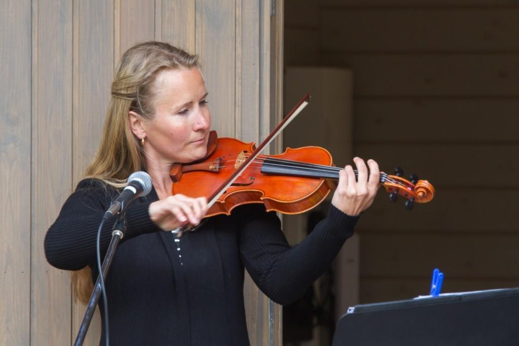 Nainen soittaa viulua seisten